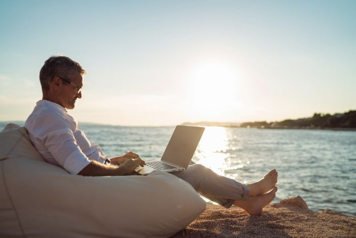 man on laptop on the beach